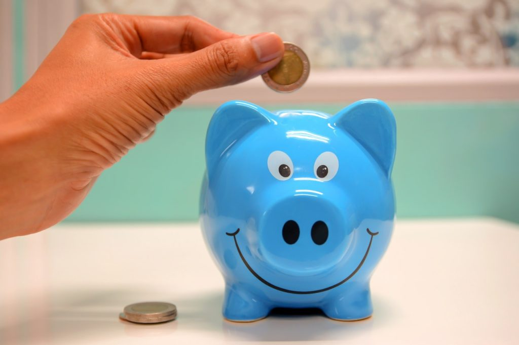 save money to move abroad, blue money pig with person holding coin