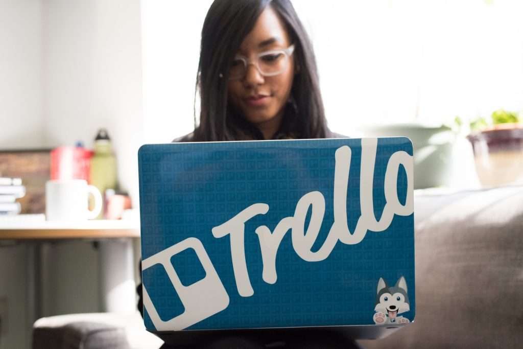 tools for a remote internship woman working on laptop with Trello sticker